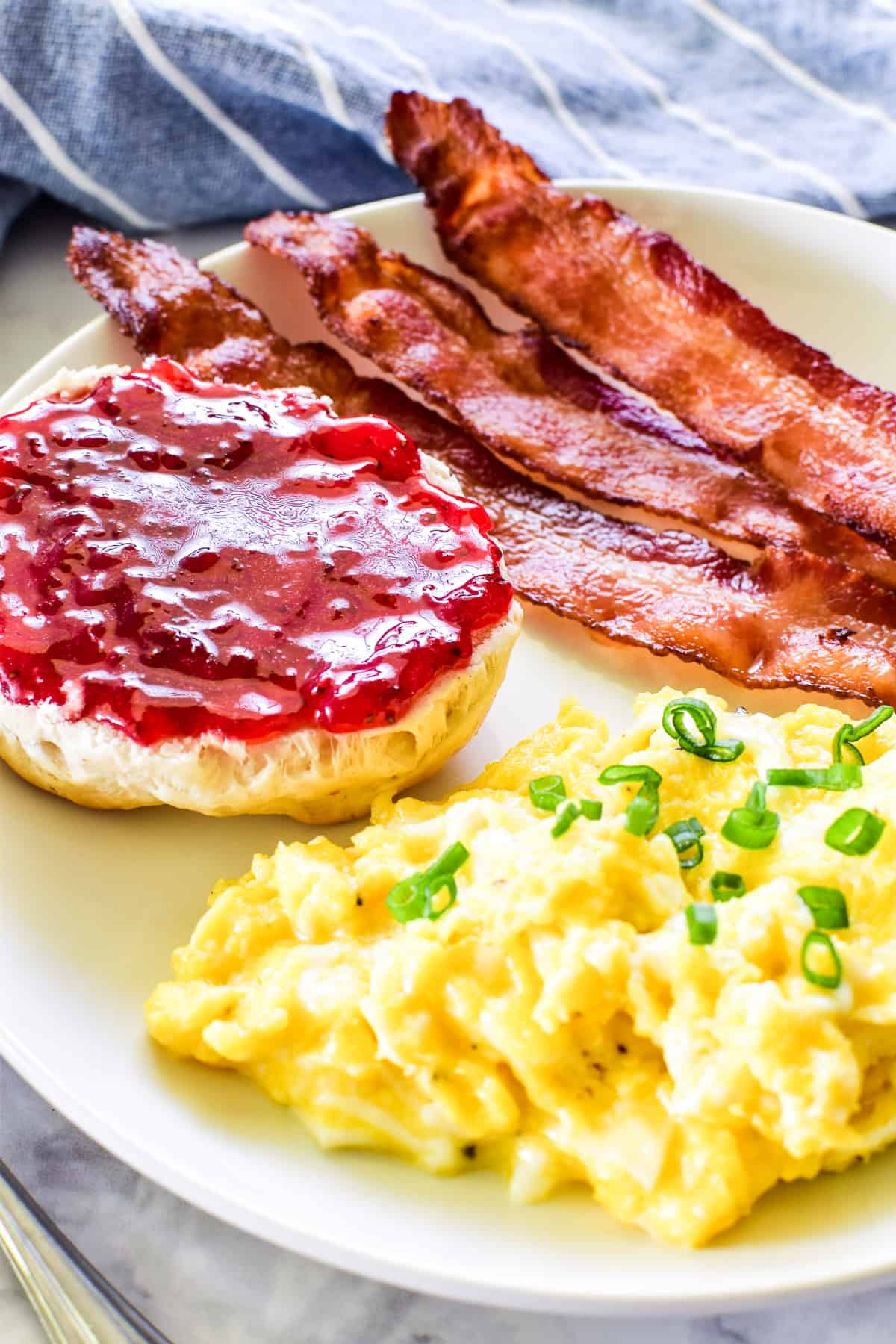 Scrambled eggs, bacon, and a biscuit with jam on a white plate