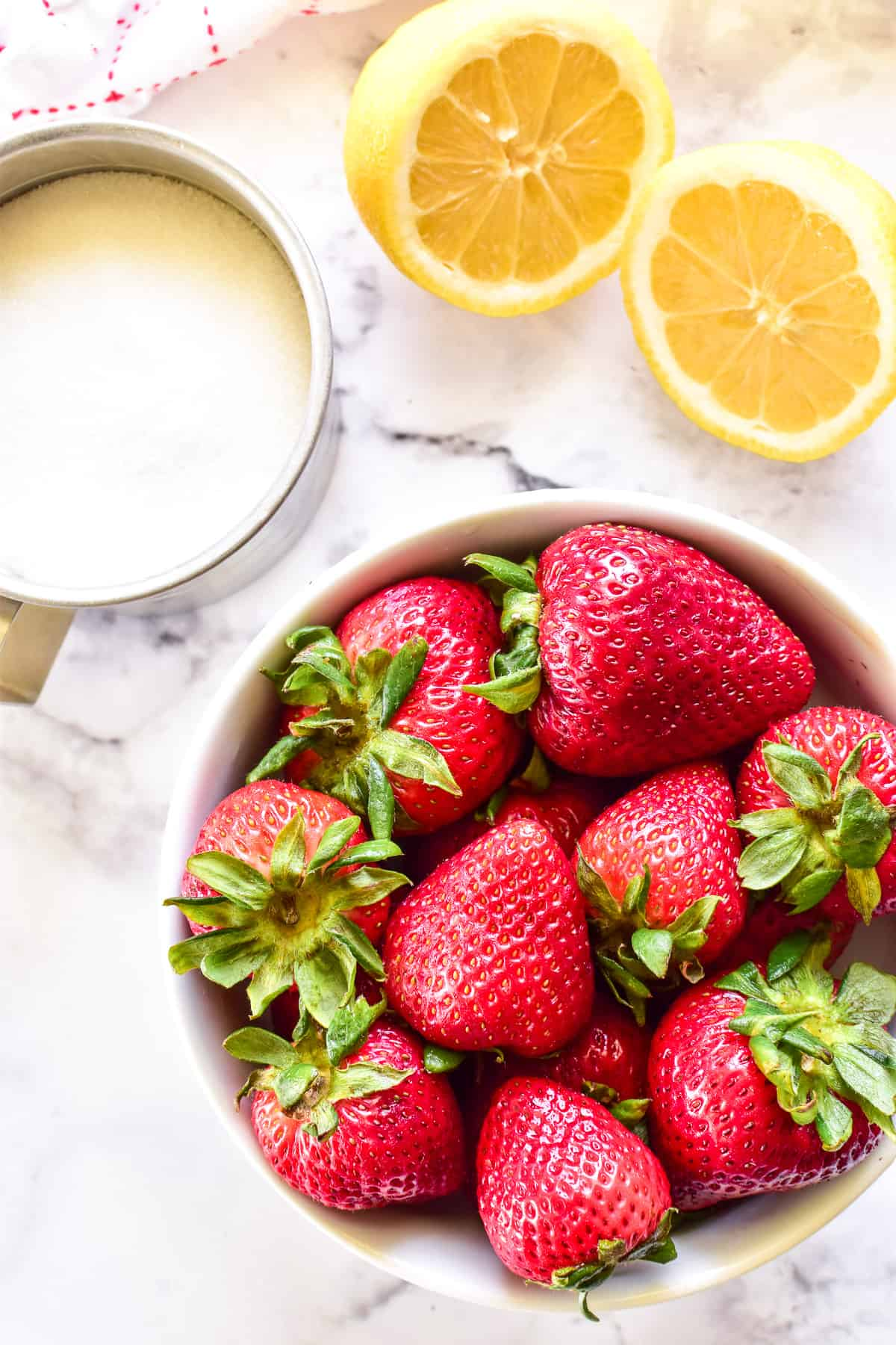 Bowl of strawberries with sugar and lemons