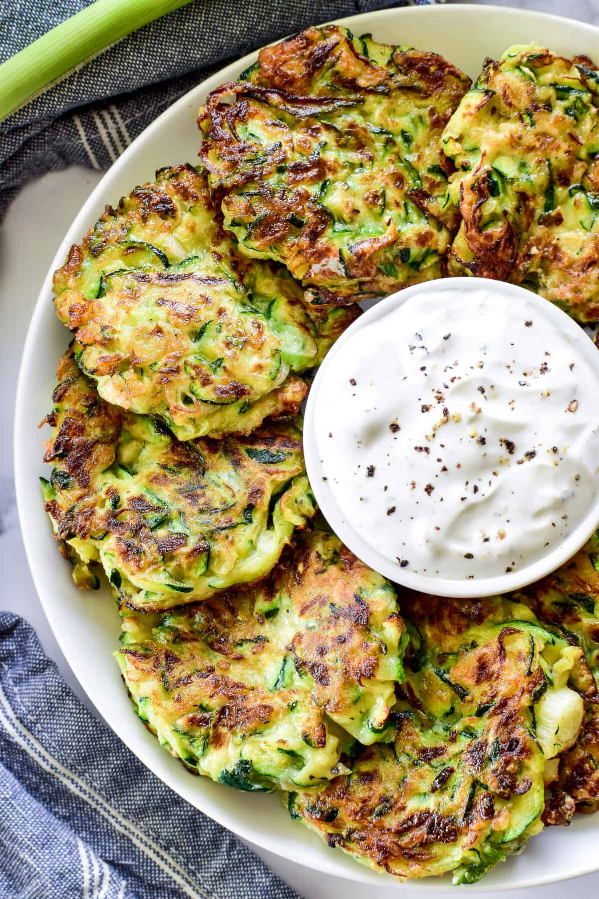 Overhead shot of zucchini fritters on a plate with dipping sauce in the middle