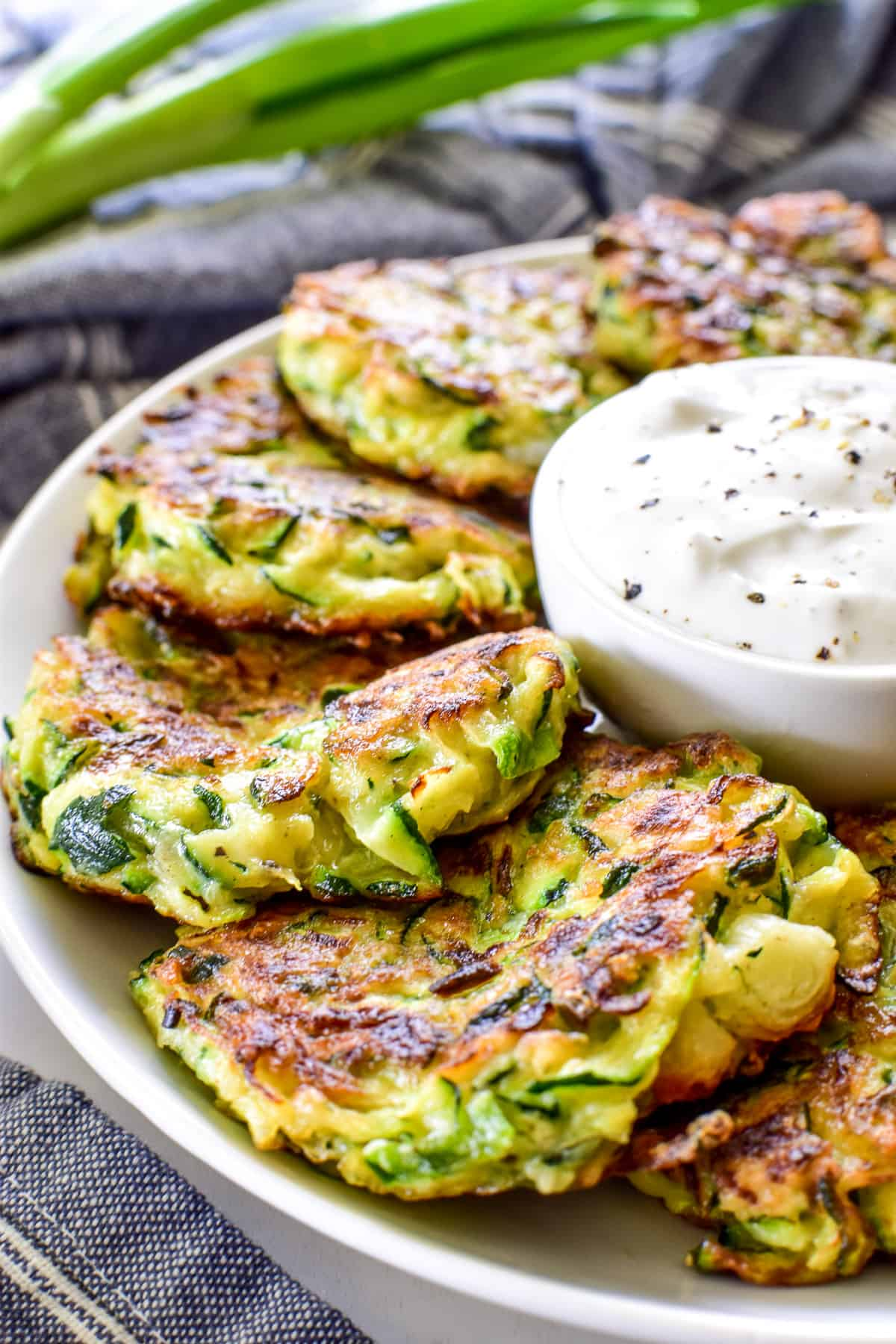 Zucchini Fritters on a serving plate with dipping sauce