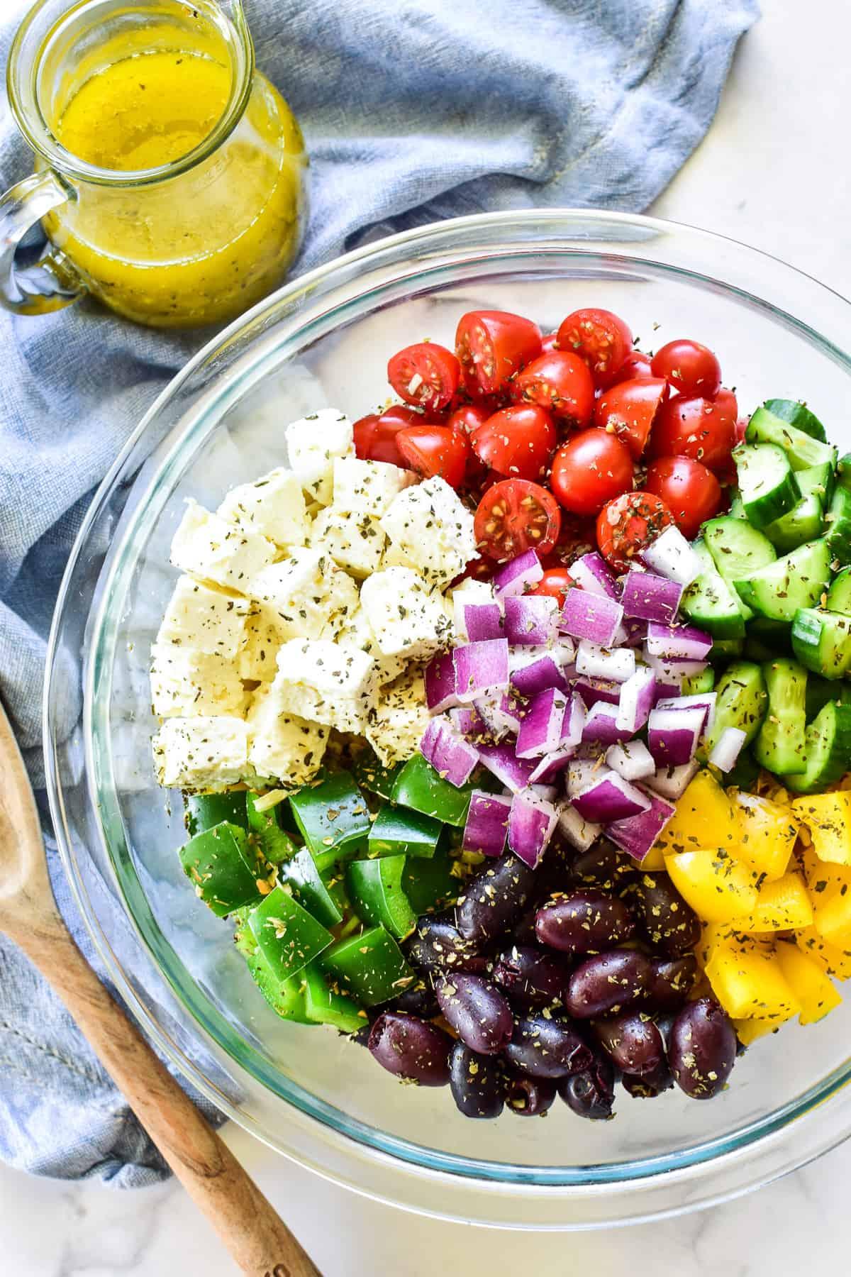 Greek Pasta Salad ingredients in mixing bowl