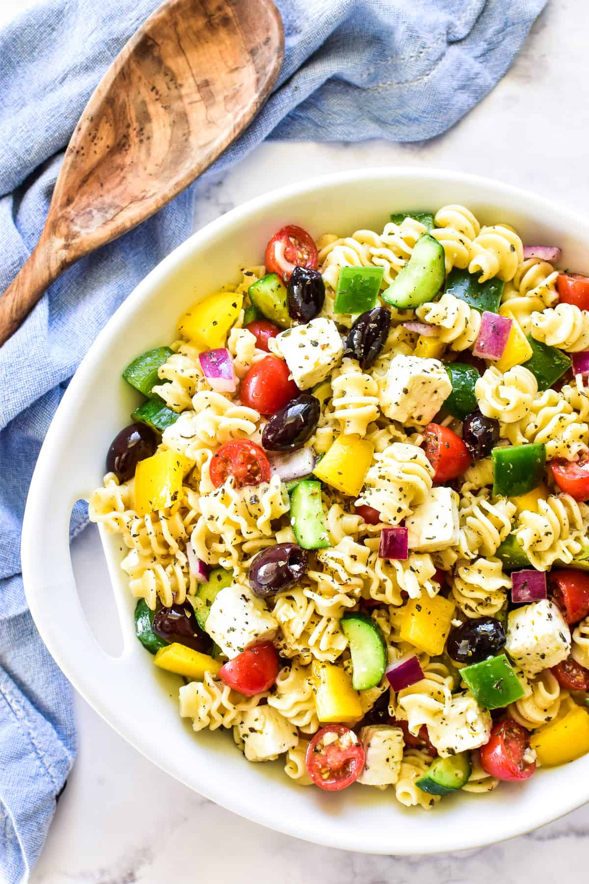 Overhead shot of Greek Pasta Salad in white serving bowl with wooden spoon
