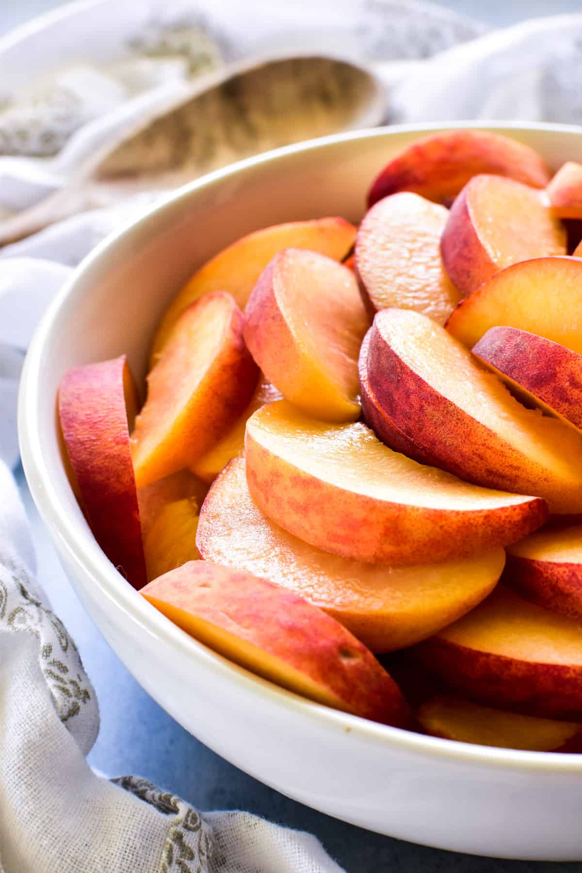 Sliced peaches in a white bowl