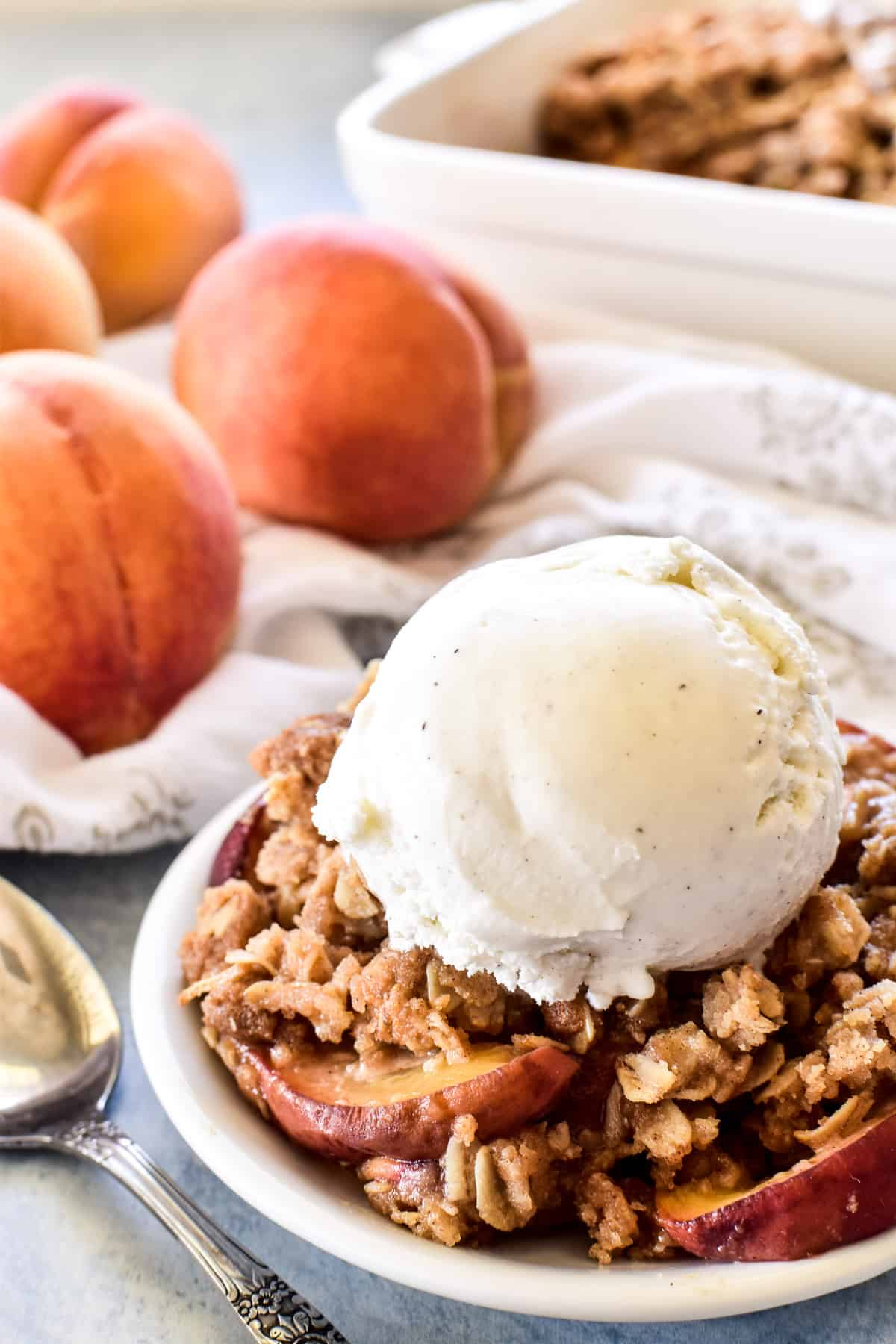 Peach Crisp on a plate with a scoop of vanilla ice cream
